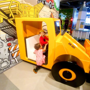 Boy and girl sitting in toy bulldozer