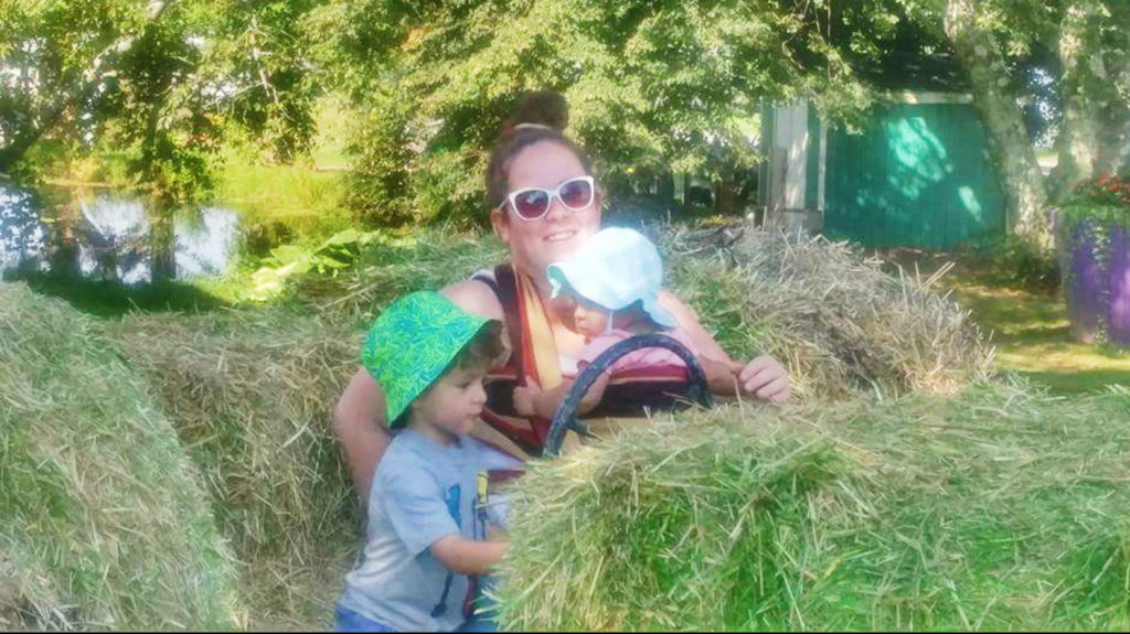 woman with baby in wrap and toddler sit on hay bales